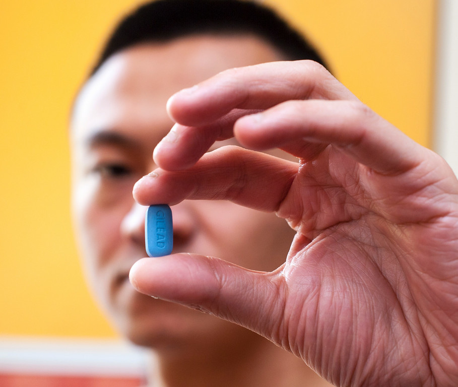 Man Holding Truvada Pill, HIV Anti-Viral medication, in Hand
