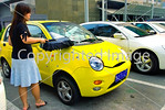 Beijing, CHINA- Chinese Woman Dusting off her Chery- Chinese Made Car in Parking lot of Business Center Directphoto