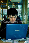 Paris, FRANCE -  Young Chinese Man Using WI Fi Wireless Internet Technology on Personal Laptop Computer in Cafe- Restaurant,.